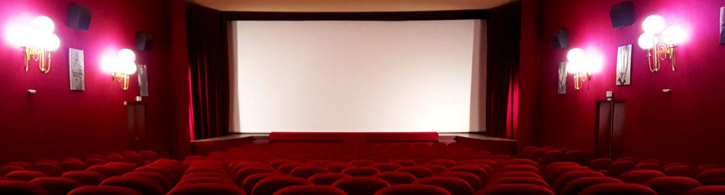 Vue depuis le centre de la salle de cinéma avec l'écran au fond