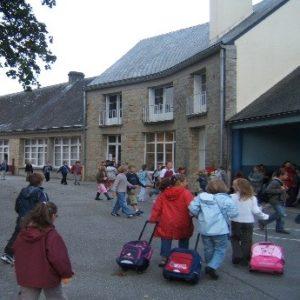 Cour de l'école primaire Léopold DELISLE avec des enfants et leurs cartables.
