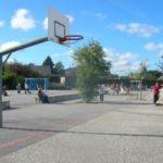 Panier de basket dans la cour de l'école primaire du Quesnay et des enfants en arrière plan