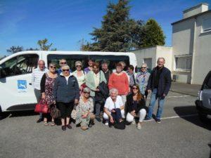 Groupe de séniors prêts à partir en vacances, devant le minibus, sous un ciel bleu