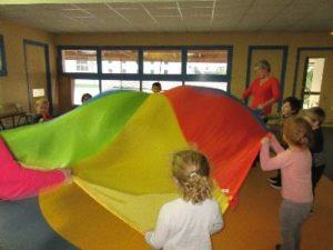 Enfants agitant un grand drap multicolore