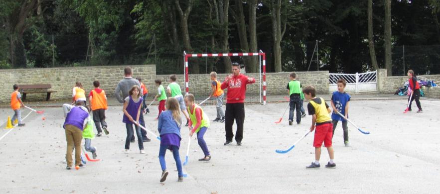 Enfants qui jouent au hockey sur gazon dans la cour de l'école, encadrés par l'éducateur sportif