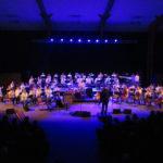 Vue d'ensemble d'un concert de l'harmonie dans une ambiance lumineuse mauve