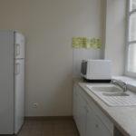 Vue du local technique de la salle Léopold DELISLE avec évier, réfrigérateur, rangements et micro-ondes.