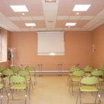 """Vue de la salle Léopold DELISLE, en configuration """"assemblée"""", chaises vertes disposées face à une table. Un écran vidéo mural est déployé au fond de la salle."""