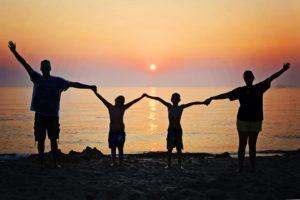 Famille levant les bras et se tenant par les mails, sur une plage. En arrière-plan la mer et un couché de soleil.
